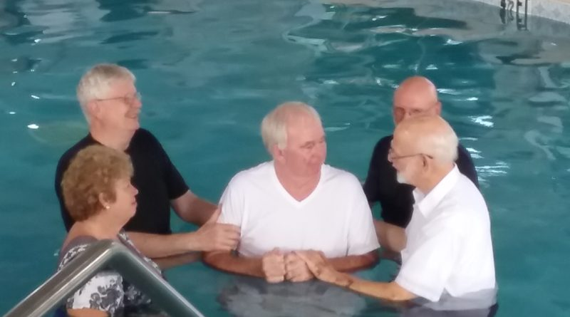 Husband and wife do full immersion Baptism together.
